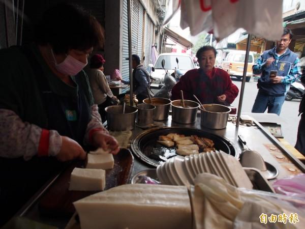 鄭秋琴一個早上片刻不停得切、煎蘿蔔糕。(記者王秀亭攝)