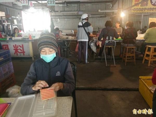 林太太剛出院,就拖著虛弱的身體到市場工作,在水餃盒上做記號。(記者黃文瑜攝)