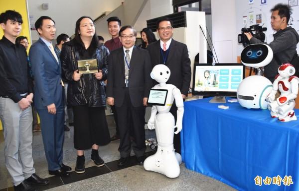 政務委員唐鳳(左三)、副市長王明德(左四)等人仔細聆聽AI機器人展出說明。(記者李容萍攝)