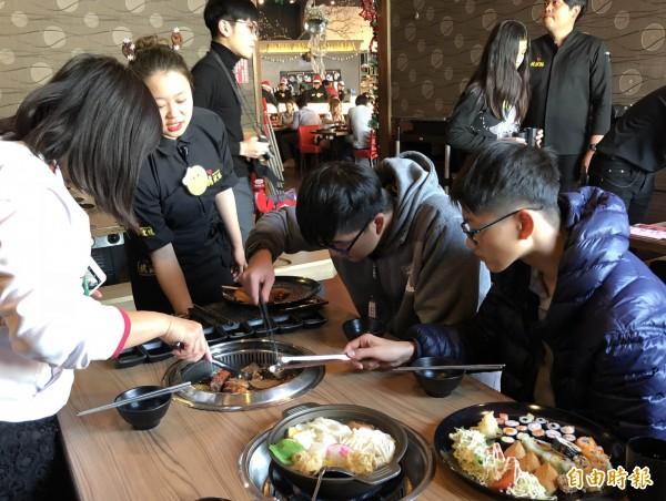 餐廳員工指導家扶兒烤肉。(記者湯世名攝)