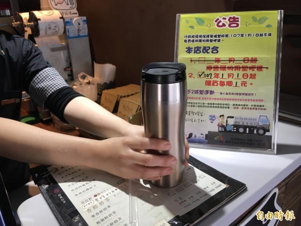 飲料店今年起不再提供購物用塑膠袋,店家公告索取必須1元購買,有民眾自備環保杯買飲料。(記者蔡淑媛攝)