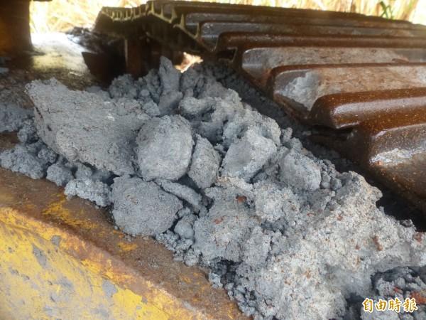 金門大學附近草叢中,發現一輛履帶沾滿疑似礦物細料的怪手工程車。(記者吳正庭攝)