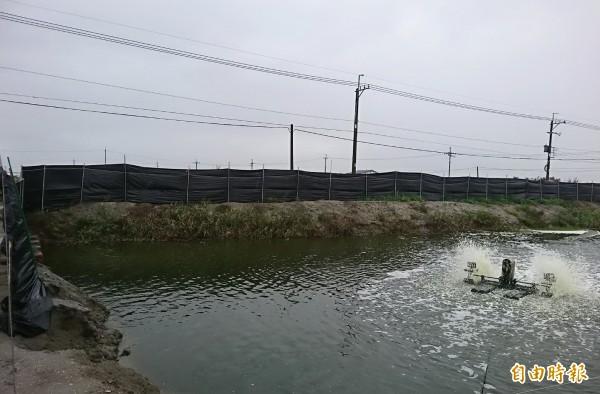 鋒面抵達後,風雲變色,台南七股魚塭紛紛啟動水車,也引水提高魚塭水位,有的加設防風網為魚塭升溫、保溫。(記者楊金城攝)