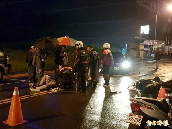 機車騎士躺在地上無法動彈,路人撐傘上前關切。(記者鄭景議攝)