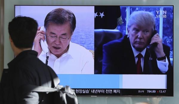 川普10日與文在寅通電話時表示,時間適當且環境正確,美國願與北韓對話。圖為去年12月1日南韓首爾民眾途經川普與文在寅熱線的電視畫面。(美聯社)
