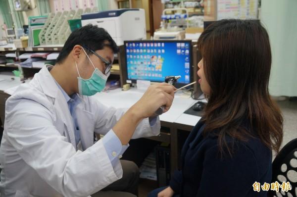 衛福部台南醫院感染科醫師為患者看感冒症狀的急診。(記者王俊忠攝)