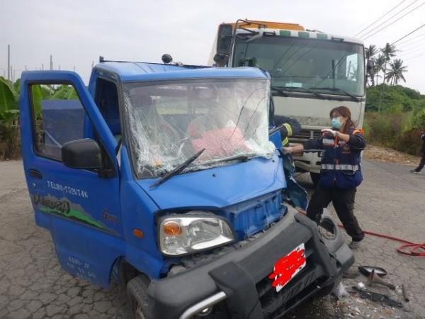 萬丹鄉發生一起大貨車撞小貨車事故,小貨車頭幾乎被撞扁,駕駛夾在變形的車頭內動彈不得,消防人員據報後到場,動用破壞工具才將受傷的曹姓駕駛送醫。(記者李立法翻攝)