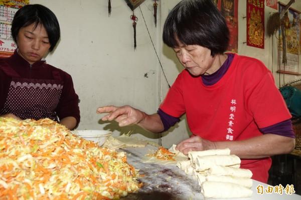 梁清涼(圖右)天天手作豆包,冬天是高麗菜、紅蘿蔔內餡。(記者劉曉欣攝)