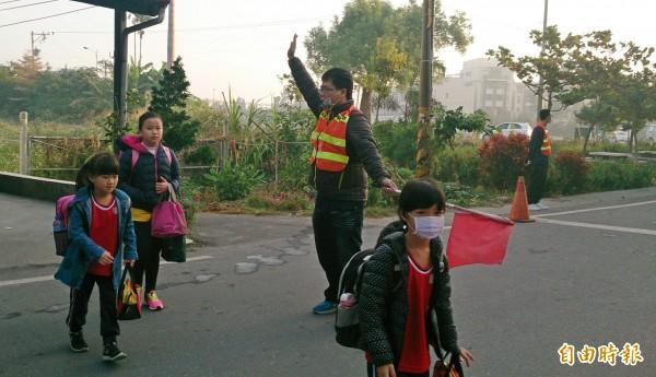 寒流強勁,溪州國小老師頂著冷風,在路口導護每位學童進入校園上課。(記者陳冠備攝)