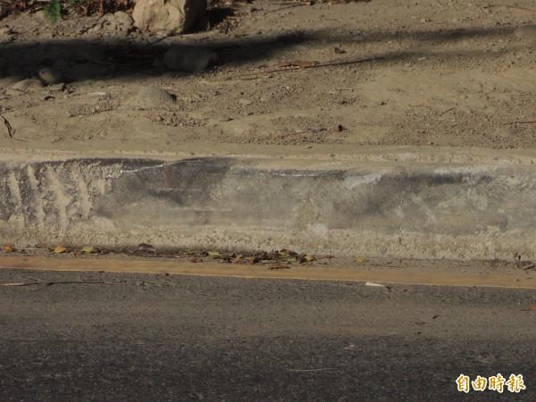 竹北市高鐵橋下六家五路2段的中央分隔島路緣石,可見許多輪胎碰撞的痕跡。(記者廖雪茹攝)