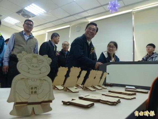 副縣長吳成典(右3)了解自造教育及科技中心現場製作的風獅爺手機架。(記者吳正庭攝)