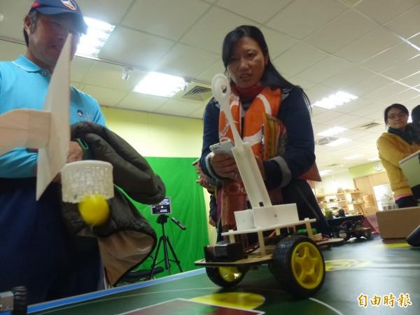 金門縣自造教育及科技中心舉行資訊教育成果展,與會者使用機器手臂「一球中網」。(記者吳正庭攝)