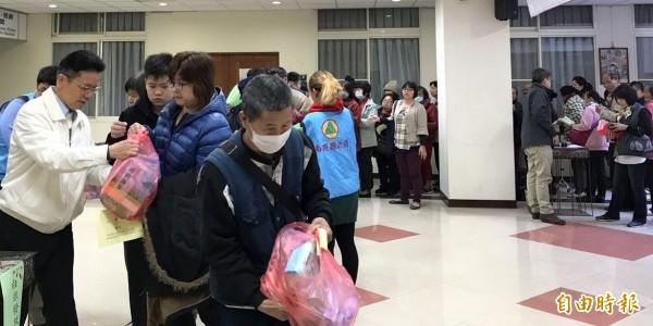 國民黨南投縣黨部主委洪榮章(左,白外套者),在「寒冬送暖、歲末傳愛」活動中,發放白米給弱勢民眾。(記者謝介裕攝)