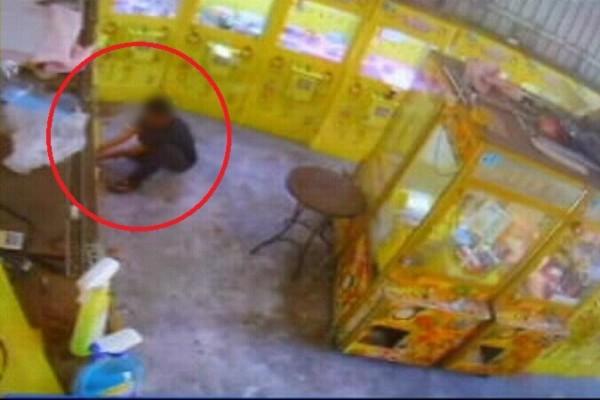 吳嫌在店內忙著徒手拆機台偷零錢。(記者許國楨翻攝)