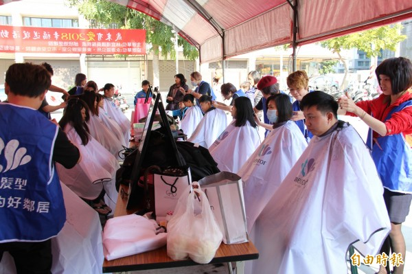 髮型設計公司,為民眾進行義剪。(記者黃文瑜攝)