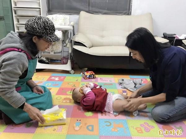 李媽媽(右)稱讚臺中市政府到宅坐月子服務的服務人員(左),在育兒方面讓她受益良多。(記者張軒哲攝)