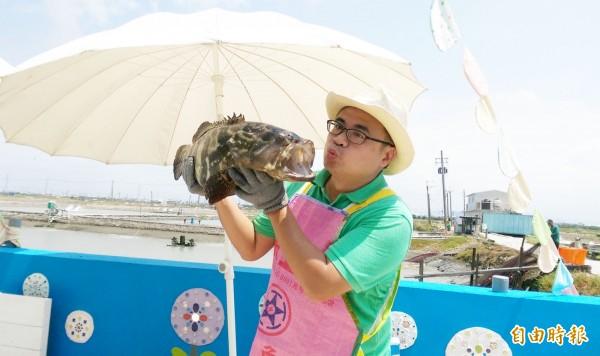遊客永安區抱石斑魚,開心合照留念。(記者陳文嬋攝)