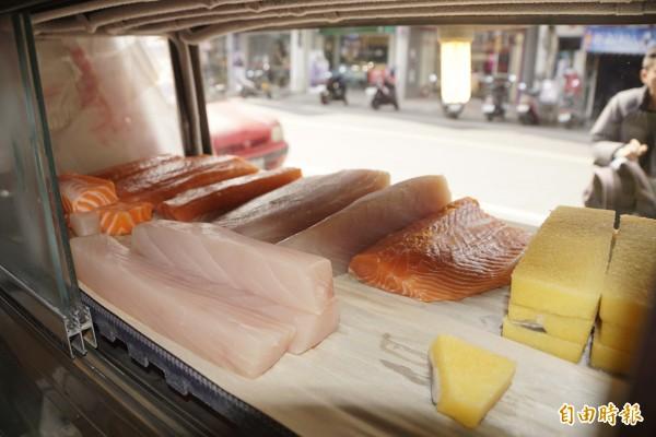 老闆謝美琳每天買進新鮮漁貨販售平價生魚片。(記者黃佳琳攝)