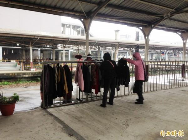 綠黨在台鐵桃園站前站發起愛心衣架活動,讓有需求的民眾挑選適合的外套禦寒。(記者陳昀攝)