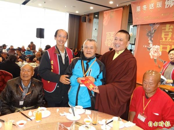 洛本天津仁波切(右三)送紅包給參與佛祖請吃飯的街友等弱勢朋友。(記者王俊忠攝)