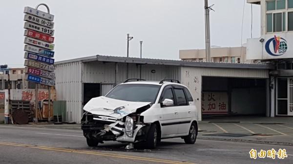 白色自小客車在加油站加完油,與重機對撞車頭毀損。(記者劉禹慶攝)