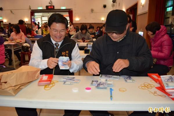 彰市農曆春節敬老禮金今天發放,市長邱建富(左)協助點鈔。(記者湯世名攝)