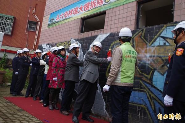 縣長李進勇(右3)象徵性用鐵鎚敲祥瑞大樓圍牆,近日展開拆除作業。(記者林國賢攝)