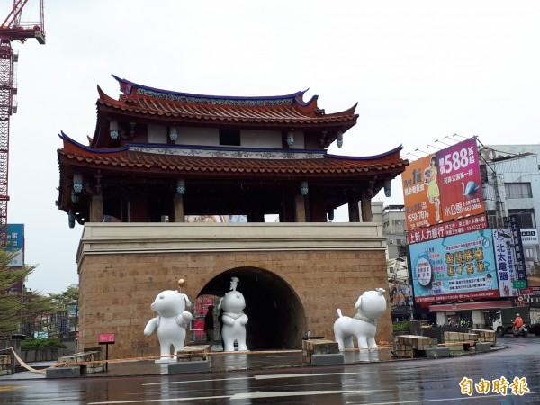 新竹市政府在東門城豎立780公分高的金色狗狗裝置藝術,造型俏皮可愛,另外在東門城前也有三隻可愛的白色狗狗造型裝置。(記者洪美秀攝)