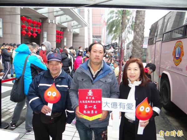 男子張絢欽(前中者)在大億麗緻酒店捐血送美食活動搶得頭香,酒店總經理嚴心誼(前右者)送上第一名熱血勇士牌。(記者王俊忠攝)