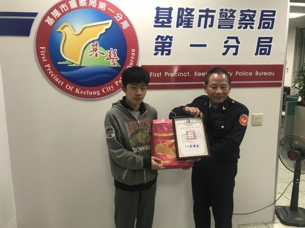基隆市警一分局長王貴正(右)致贈見義勇為的許哲銘獎牌與水果禮盒,表彰他的義行。(記者林嘉東翻攝)