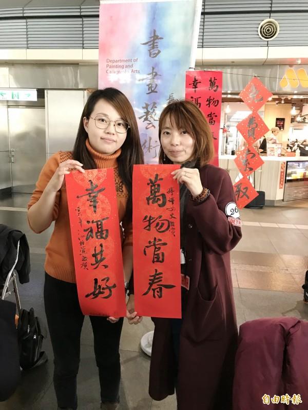 民眾慕名前來,請江柏萱(左)幫忙寫下「萬物當春、幸福共好」的春聯賀詞。(記者吳俊鋒攝)