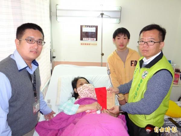 南市議員呂維胤(右1)與市府社會局人員(左1)各代表送2萬元與1萬元慰問金給陳文宏(右2)的單親媽媽(躺者)。(記者王俊忠攝)