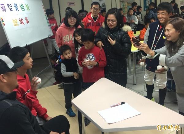 蔣智賢(左下一)為小粉絲們在球上簽名並合照,展現大哥哥的親和力。(記者吳正庭攝)