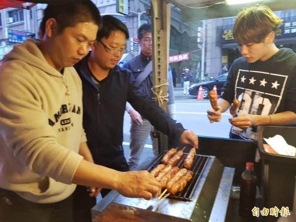 吳惠風(中)的香腸攤車,與朋友繞行半個台灣開到花蓮,今天一早提供免費烤香腸給救災人員享用。(記者俞肇福攝)