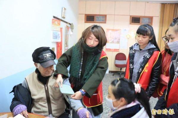 華山基金會南庄天使站站長徐敏慈帶著三灣國中的學生並幫阿公量學壓。(記者鄭名翔攝)