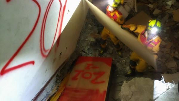 在雲門翠堤大樓丁文昌、何鳳華夫婦罹難的漂亮生活旅店201號房,花蓮縣特種搜救隊人員用噴漆做明顯記號,提醒重機械怪手一旦挖到就要停止,改以人力挖掘,務必送出完整遺體。(花蓮縣消防局提供)