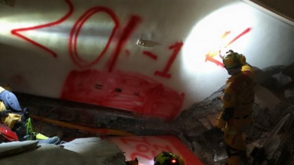 花蓮縣特種搜救隊人員用噴漆做明顯記號,提醒拆除過程中重機械一旦挖到就要改以人力挖掘,務必保持遺體完整。(花蓮縣消防局提供)