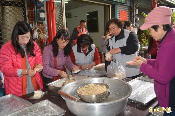 台中市大屯區成長協會今天舉辦吃元寶賀新春活動,志工合力包了3千顆水餃和社區民眾同樂。(記者陳建志攝)