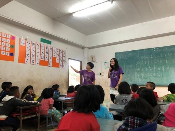 國立金門大學陽光天使社長李辰恩(站者右)等人組成的服務團隊,遠赴泰北「異域」服務當地華人學生。(圖由金門大學提供)