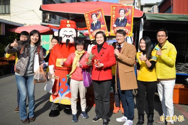 有意參選新竹縣長的民國黨主席徐欣瑩(右四)今天到竹北市場發春聯。(記者蔡孟尚攝)