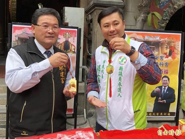 彰化市長邱建富(左)、市代楊富鈞(右)歡迎信眾索取健康招財錢母掛飾與功名富貴燈。(記者湯世名攝)