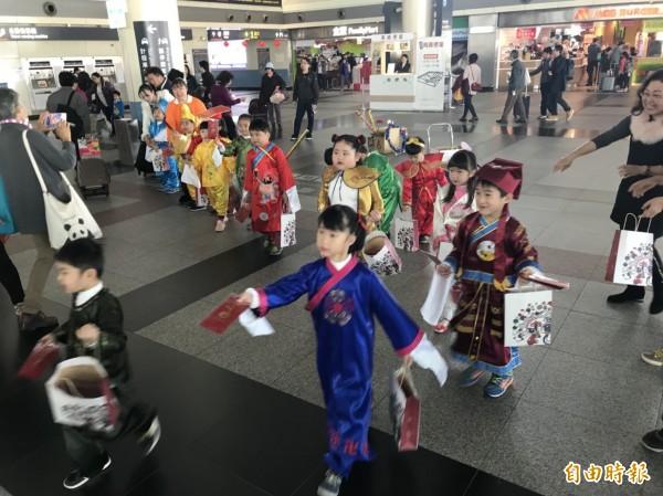 曉明幼兒園學童在高鐵嘉義站發紅包袋。(記者林宜樟攝)