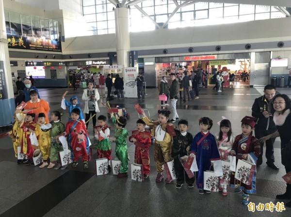 曉明幼兒園學童穿上刺繡服裝打扮成神仙,在高鐵嘉義站發紅包袋。(記者林宜樟攝)