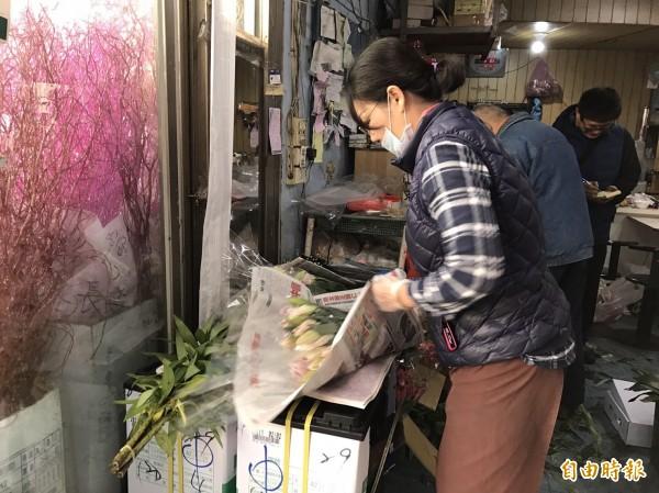 今天西洋情人節,又逢小年夜,花店業者忙打包消費者購買的花卉。(記者湯世名攝)