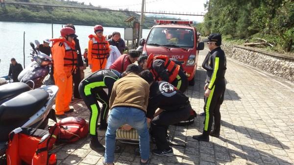 消防隊員合力將落海的漁夫救起,送往澳底保健站搶救。(記者吳昇儒翻攝)