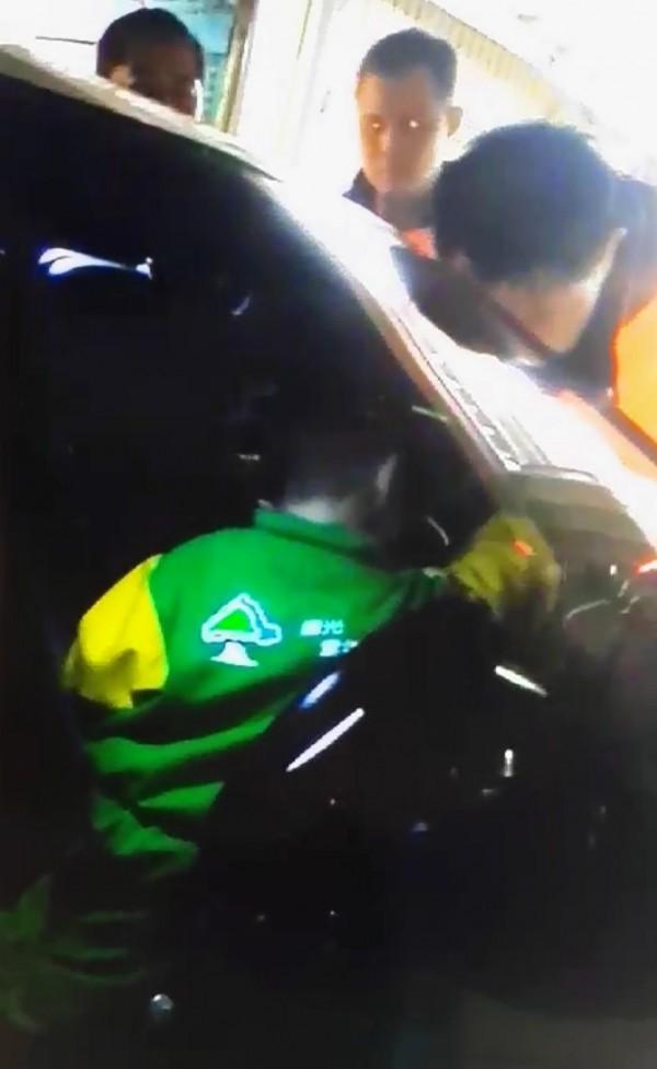 員警用雷射筆的紅光指引男童來打開車內中控鎖。(記者楊金城翻攝)