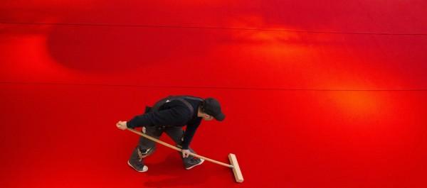 第68屆柏林影展15日正式開幕,一名工作人員13日在做最後準備工作時,將影展會場外的紅地毯推平。(歐新社)