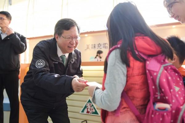 桃園市長鄭文燦發放福袋給搭車的旅客。(市府提供)