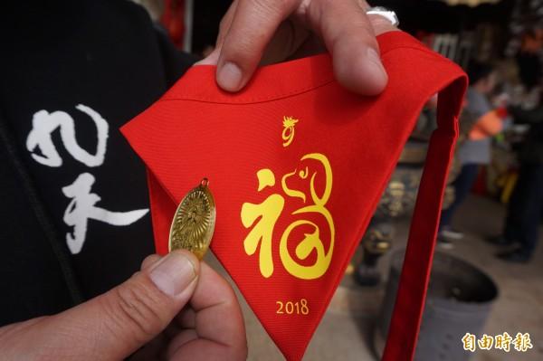 九天民俗技藝團為寵物特製的平安紅包,包括喜氣的寵物用三角巾及九天玄女娘娘紀念墜子(後方貼有一元硬幣)。(記者歐素美攝)