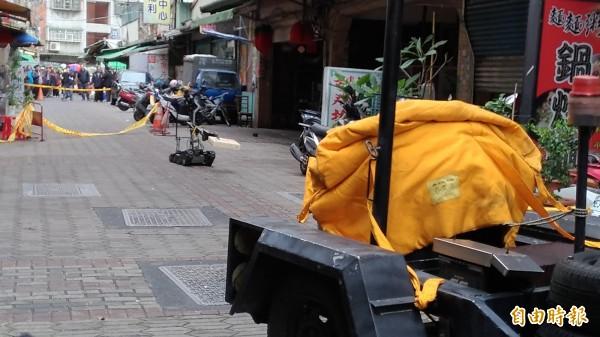 防爆小組以機器人將疑似爆裂物夾進防爆桶,裡頭證實塞滿「垃圾」。(記者鄭淑婷攝)
